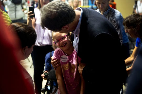 Steve Bullock, Governor of Montana, poses for a photo with a young girl at Confluence Brewing Company on Thursday, May 16, 2019, in Des Moines. This is Bullock's first visit to Iowa after announcing his 2020 bid.