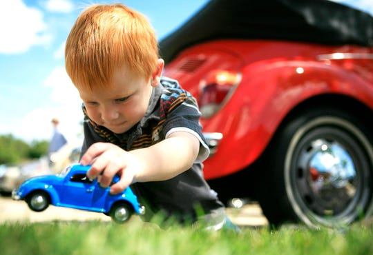Jerry Adams, 3, plays with a toy Volkswagen Beetle while his dad's 1973 convertible Super Beatle is parked behind him in Bloomfield Hills during the Woodward Dream Cruise in this file photo from August 16, 2008.