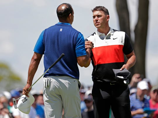 Brooks Koepka, right, shakes hands with Tiger Woods after finishing the first round of the PGA Championship golf tournament, Thursday, May 16, 2019, at Bethpage Black in Farmingdale, N.Y. (AP Photo/Julio Cortez)