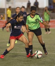Islanders FC's Krystiana Martinez tries to stay in control of the ball in the midfield against Quality Distributors in first round action of the Jamaican Grill Annual Women's GFA Cup May 5 at the Guam Football Association National Training Center. The Islanders upset Quality 2-1.
