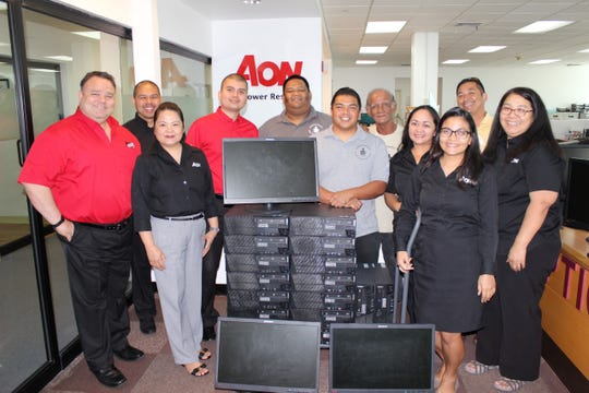 Aon Insurance Micronesia (Guam) Inc. and Sanctuary Incorporated staff pose for a photo upon receiving their donation of computers at the Aon Insurance office on May 16, 2019.