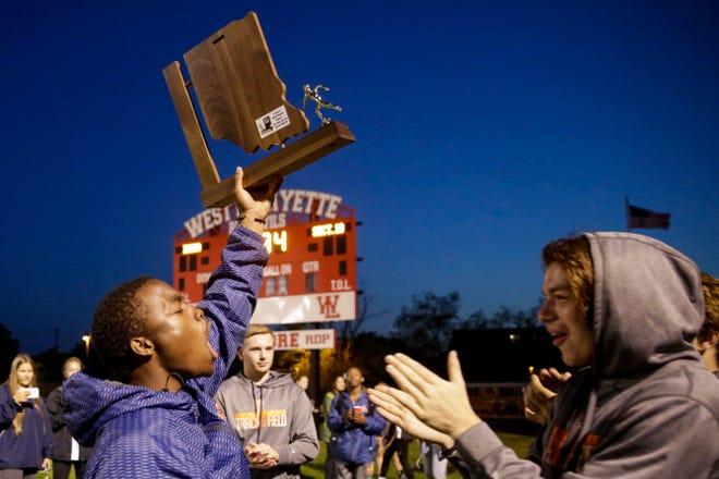 Harrison's Isaac Armstrong hoists up their IHSAA boys track sectional trophy, Thursday, May 16, 2019 in West Lafayette.