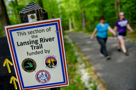 A sign posted on the trail at Hawk Island shows what organizations funded the Lansing River Trail on Thursday, May 16, 2019, in Lansing.