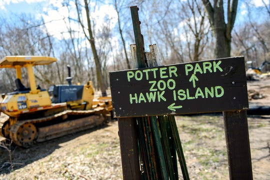 A crew works on a portion of the Lansing River Trail on Friday, April 12, 2019, near Potter Park Zoo in Lansing. Ingham County in March will ask voters to approve millages to support trails and parks and Potter Park.