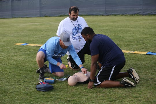 Rocky Fork Middle head football coach David Cowan (right) and assistants Zane Perry (center) and Eric Osborn perform sudden cardiac arrest training on a dummy at the school's practice field Wednesday.