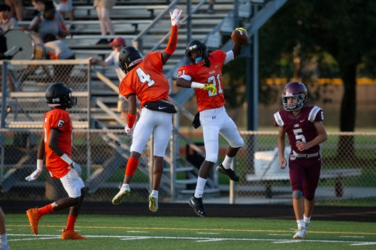 Lely High School's Chevy Octa, left, Ben Dumond celebrate a touch down by teammate Sergio Morancy during their game against First Baptist Academy, Thursday during a three-way spring jamboree exhibition game at Lely High School.