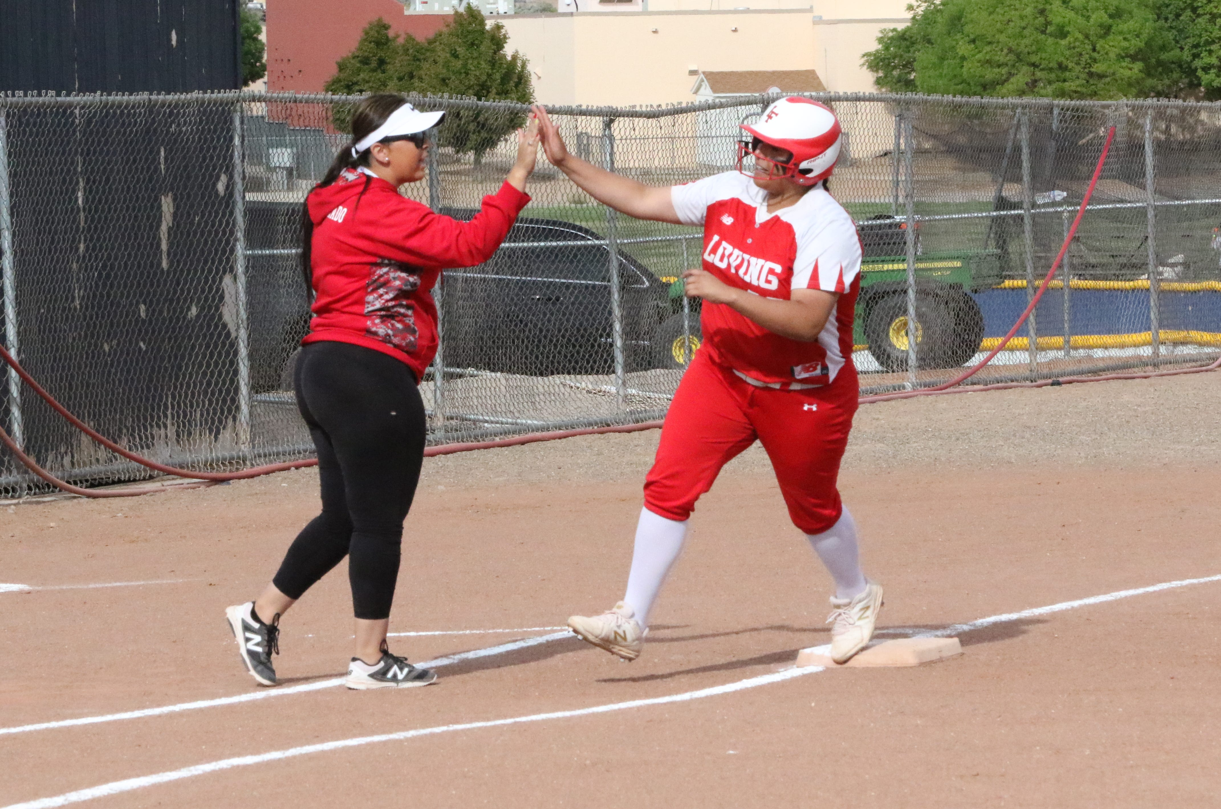 Loving's Lorisa Martinez high-fives coach Kendra Granado after hitting one of her two home runs against Lordsburg on Thursday, May 16. Loving won, 15-0.