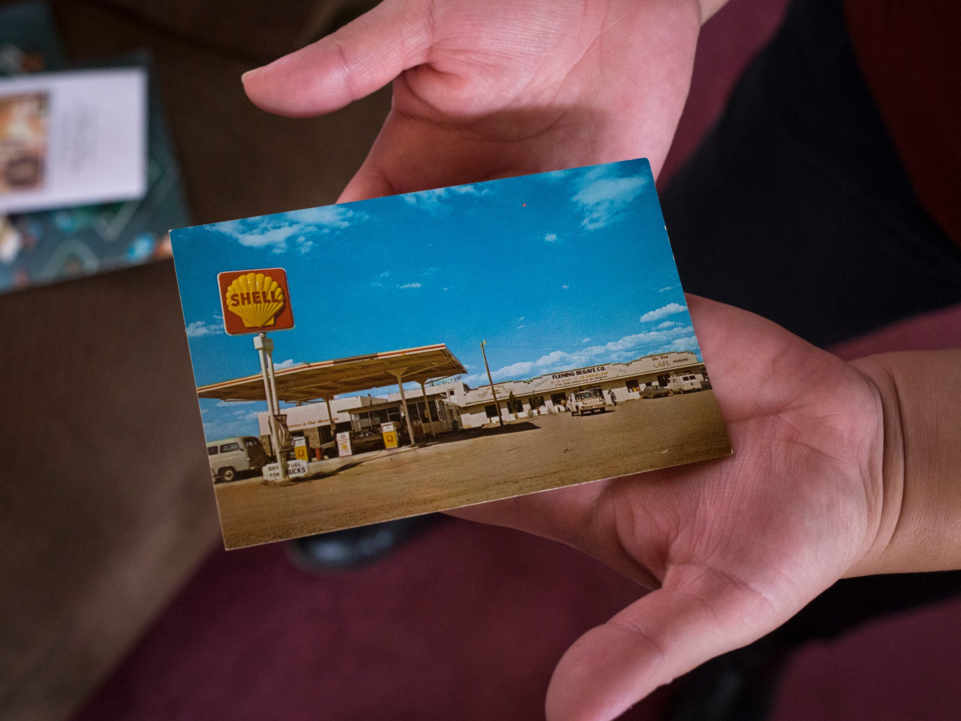 Theodosia Ott (granddaughter) holds a postcard of the gas station Fleming Begaye Sr. used to operate.