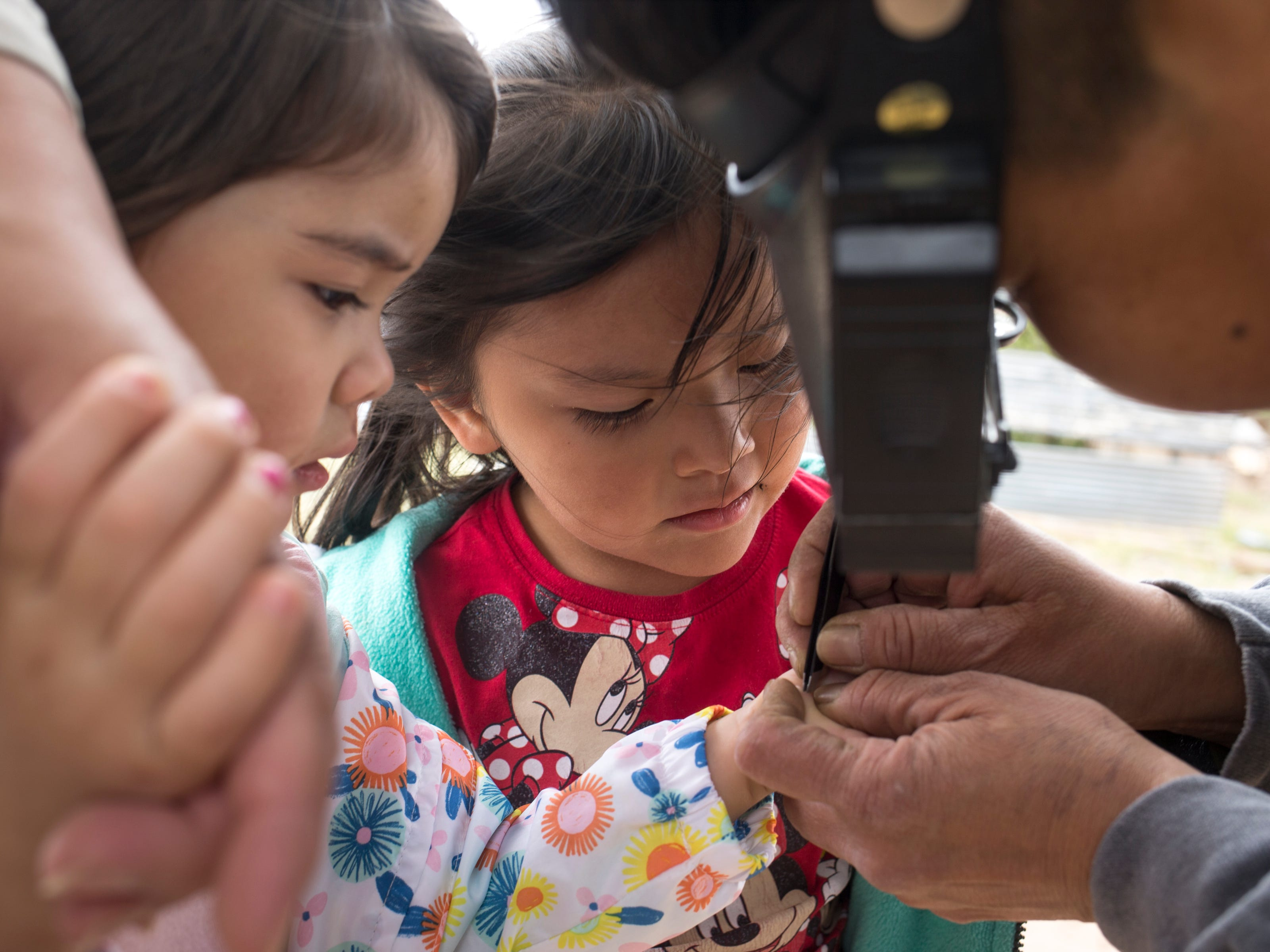 Terry Oliver (granddaughter, right) removes a sticker from the hand of Oona Ott (great-granddaughter, left), May 16, 2019, on the Begaye family farm in the Salt Water Canyon, east of Many Farms, Ariz. Looking on is Zara Oliver (great-granddaughter, center).