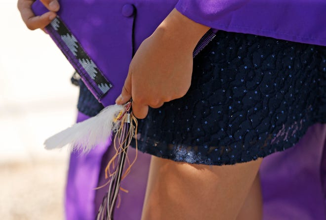LaRissa Waln holds her cap she decorated as she protests outside State Farm Stadium where Valley Vista High School holds their graduation in Glendale, Ariz., on May 16, 2019. The school would not allow any decorations on their caps or gowns.
