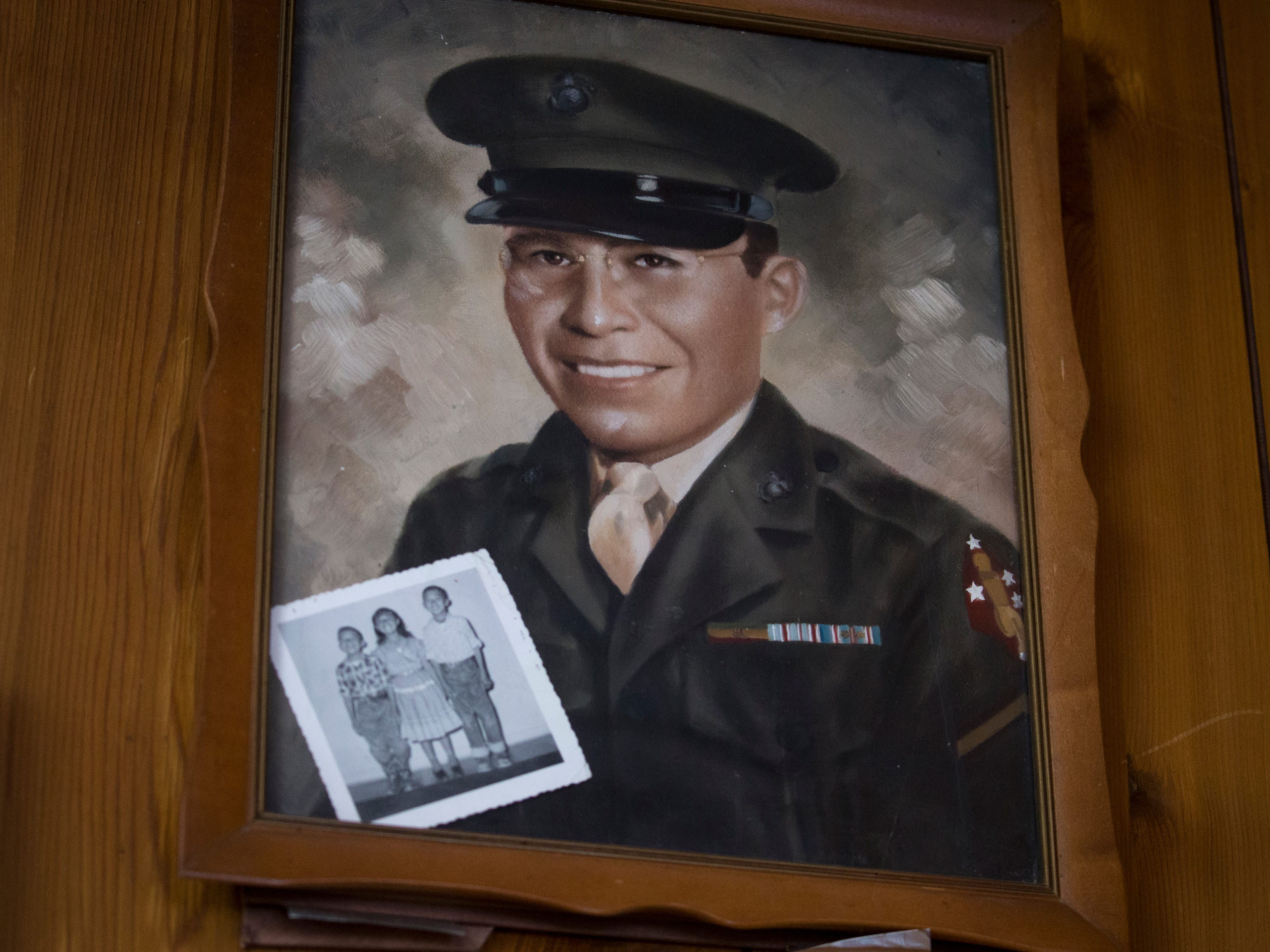 A photo of Navajo Code Talker Fleming Begaye Sr. and his children (black and white) hangs on the wall in the Begaye family home on Chinle, Ariz.