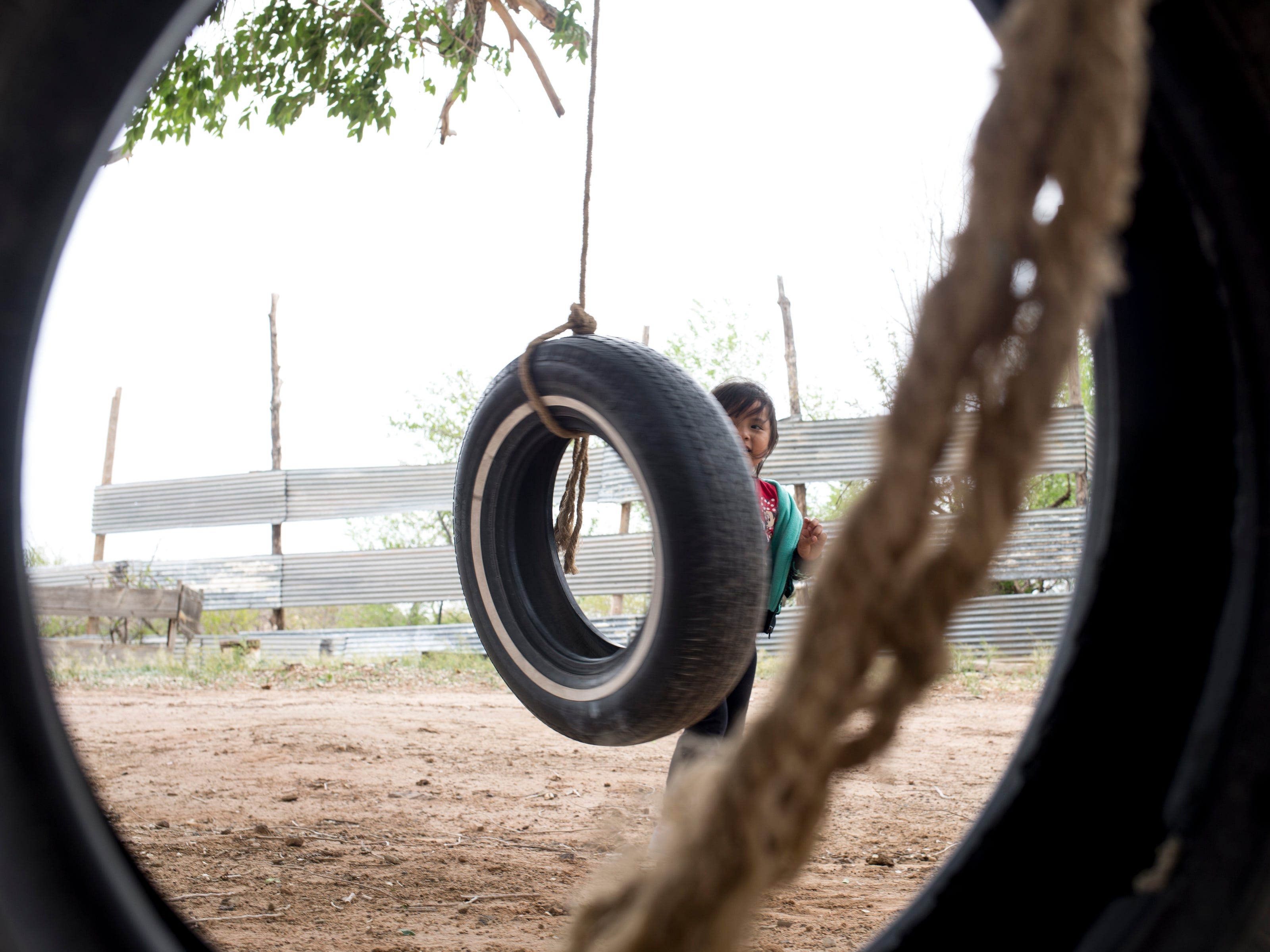 Zara Oliver (great-granddaughter) plays with a tire swing, on the Begaye family farm in the Salt Water Canyon, east of Many Farms, Ariz., on May 16, 2019.