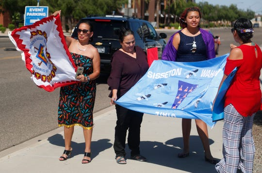 Troi Waln (left), LaRissa Waln's aunt, protests outside State Farm Stadium where her niece's graduation was being held in Glendale, Ariz., on May 16, 2019. Larissa Waln (in purple gown) was not allowed to walk with a decorated cap.