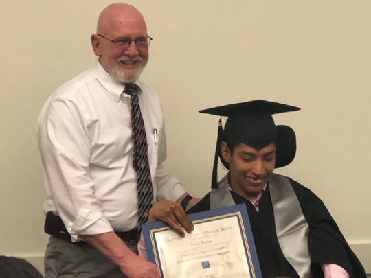 Jesse Rojas with the Nevada University Center for Excellence in Disabilities Director Stephen Rock on graduation night.