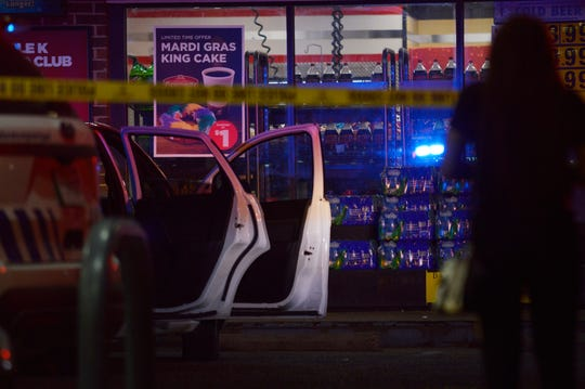 A white four-door car is seen behind police tape Thursday night outside a Circle K store located at Jewella Avenue and W 70th Street.