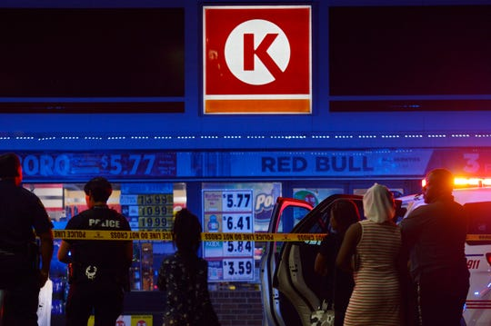 People are seen standing in a parking lot Thursday night outside a Circle K store located at Jewella Avenue and W 70th Street.