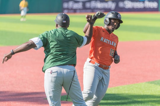 FAMU assistant/third base coach Anthony Robinson congratulates Kaycee Reese after hitting a 2-run homer versus Norfolk State in day two of the MEAC Baseball Championship at Jackie Robinson Ballpark in Daytona Beach.