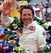 Mario Andretti waves from the winner's circle after winning the  1969 Indianapolis 500.
