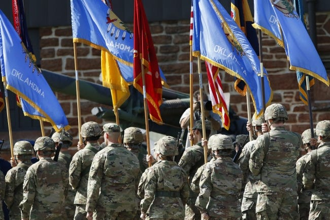 Troops march carrying flags in 2018 in front of the stage at the start of the 45th Infantry Division Museum's annual Memorial Day Ceremony at the 45th Infantry Division Museum in Oklahoma City. [Oklahoman Archive Photo]