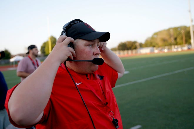 Del City coach Mike Dunn adjusts his headset during a high school football game between Del City and Bishop McGuinness in Del City, Okla., Friday, Sept. 6, 2019. [Bryan Terry/The Oklahoman]