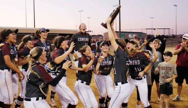 Edmond players jump with the trophy during the 6A Fast Pitch Championship game between Edmond Memorial and Owasso at the Ball Fields at Firelake in Shawnee, Saturday, October 19, 2019. [Doug Hoke/The Oklahoman]