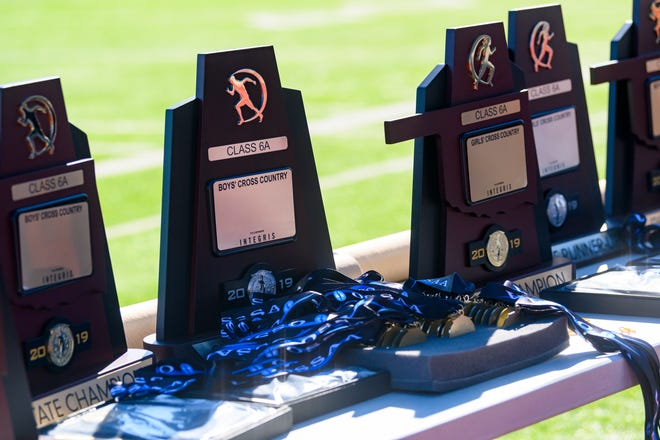 Trophies sit on a table before awarded to winners of the 5A/6A OSSAA Cross Country State Championship held at Edmond Sante Fe in Edmond, Okla., on November 2, 2019. Photo by KT King, For the Oklahoman