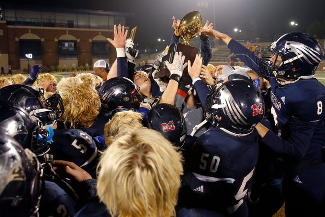 Tulsa Metro Christian celebrates with the trophy after the Class 2A football state championship game between Tulsa Metro Christian and Vian at Wantland Stadium in Edmond, Okla., Saturday, Dec. 14, 2019. [Bryan Terry/The Oklahoman]