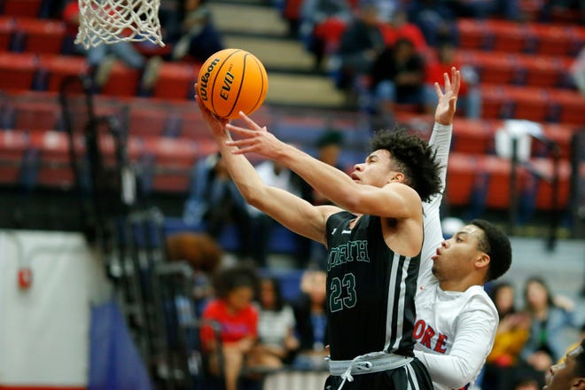 Norman North's Caeline Hearne goes to the basket past Moore's Justin Martin during a high school basketball game between Moore and Norman North in Moore, Okla., Tuesday, Jan. 21, 2020.[Bryan Terry/The Oklahoman]