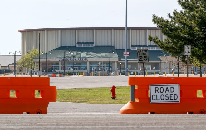 """Jim Norick State Fair Arena, """"The Big House,"""" is seen behind barriers at the entrance to the OKC Fairgrounds from May Ave. at Gordon Cooper Blvd. in Oklahoma City, Thursday, March 26, 2020. The Oklahoma City-County Health Department has partnered with a private lab to test high-risk individuals for the new coronavirus at a drive-thru facility at the fairgrounds. Tests will only be given to patients with a doctor's referral and appointment. [Nate Billings/The Oklahoman]"""