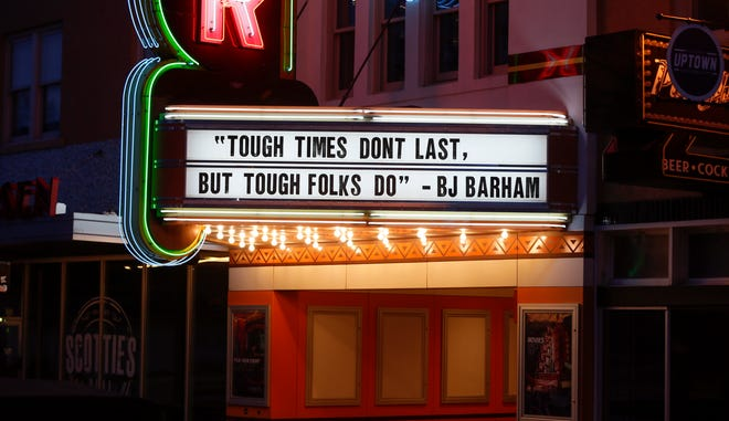 """The marquee on the closed Tower Theatre displays the lyric """"Tough times don't last, but tough folks do,"""" by BJ Barham in the vacant Uptown district along NW 23 between Walker Ave. and Hudson Ave. on what would normally be a busy night for bars and restaurants in Oklahoma City, Thursday, March 26, 2020. [Nate Billings/The Oklahoman]"""