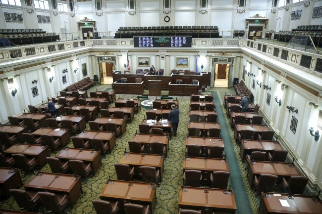 A skeleton crew of lawmakers are seen April 6 inside the House chamber during a special session of the House of Representatives. Others watched from their offices during the special session. [Bryan Terry/The Oklahoman]