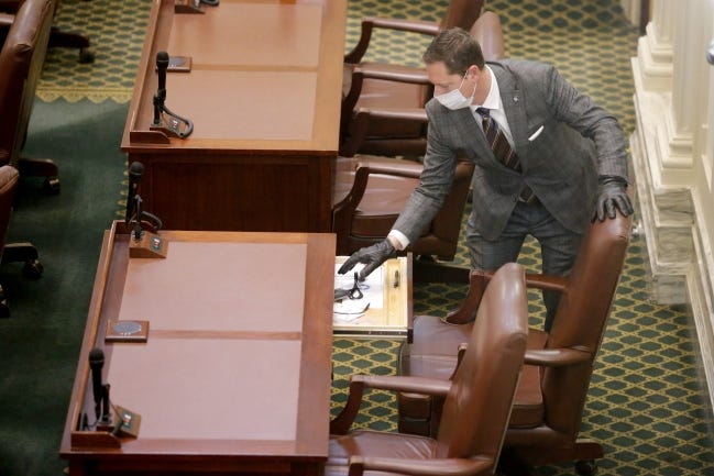 In this April 6 photo, a masked Rep. Brian Hill looks inside his desk before a special session of the House of Representatives at the state Capitol. A skeleton crew of lawmakers was allowed in the House chamber as others watched from their offices. [Bryan Terry/The Oklahoman]