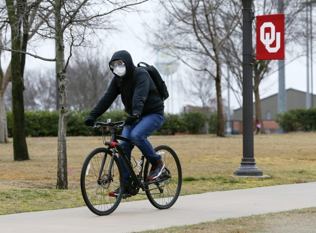 A cyclist wears a mask and goggles last March while riding along a sidewalk on the University of Oklahoma campus in Norman. Oklahoma universities say the admissions process is different but not necessarily harder since the pandemic began. [The Oklahoman Archives]