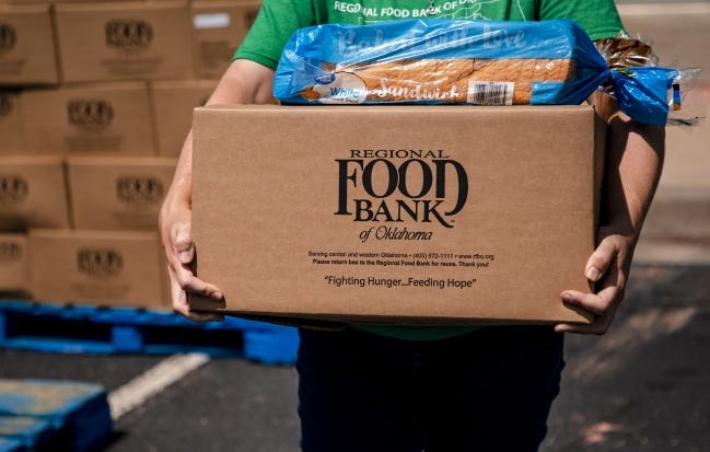 Katelyn Gleason-Dockery prepares to load a box of food into a clients car during the Regional Food Bank of Oklahoma food distribution event for individuals seeking unemployment assistance on Wednesday, July 8, 2020, in Midwest City, Okla. [Chris Landsberger/The Oklahoman]