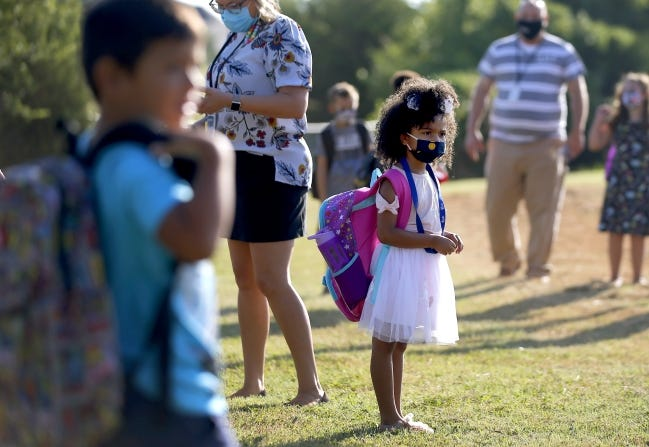 Kindergartner Aubree Freeman, 6, waits in line after she was dropped for her first day of school at Charles Haskell Elementary in Edmond on Aug. 20. Edmond Public Schools opted for a blended learning model which has students alternate between at-home learning and attending class in person. [Bryan Terry/The Oklahoman]