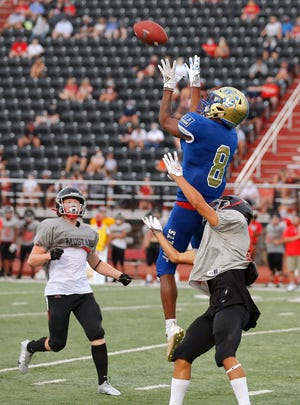 Choctaw's Terrill Davis makes a catch between Mustang's Trevor Price, left, and Karston Keene during a scrimmage in Mustang on Aug. 21. [Bryan Terry/The Oklahoman]