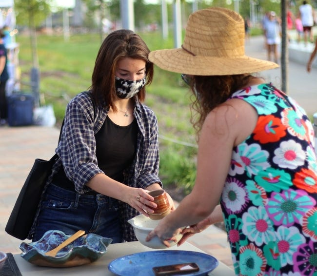 Haley Korff looks at pottery as Melissa Cobbs Leon, of H&M Pottery, on July 31 at the Night Market at Scissortail Park in downtown Oklahoma City. [Doug Hoke/The Oklahoman Archives]