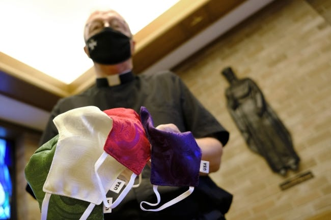 Health officials say communities where masks are mandated have fewer cases of COVID-19 than communities that don't. Here, the Rev. Rick Stansberry, pastor of Christ the King Catholic Church, holds color-coordinated masks offered to parishioners in August.  [Doug Hoke/The Oklahoman]