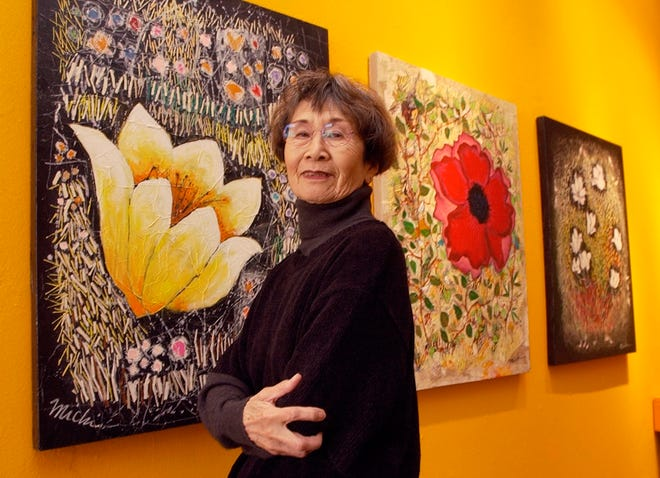 """Artist Michi Susan poses with mixed-media paintings in her """"Wildflowers"""" series in 2004 at JRB Art at the Elms in the Paseo Arts District. [The Oklahoman Archives]"""