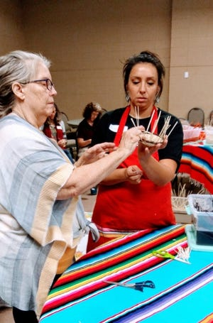 Britteny Cuevas, at right, is shown assisting a woman with a Native American basket weaving project. [PHOTO PROVIDED]