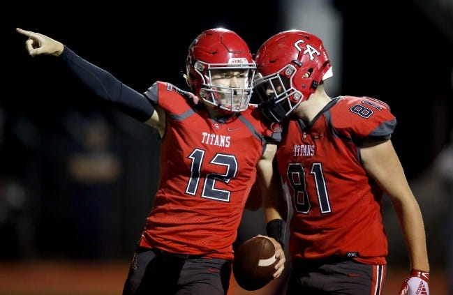Ben Harris (12) celebrates a touchdown with Charles Fleming during Carl Albert's win at Del City on Sept. 11. [Sarah Phipps/The Oklahoman]