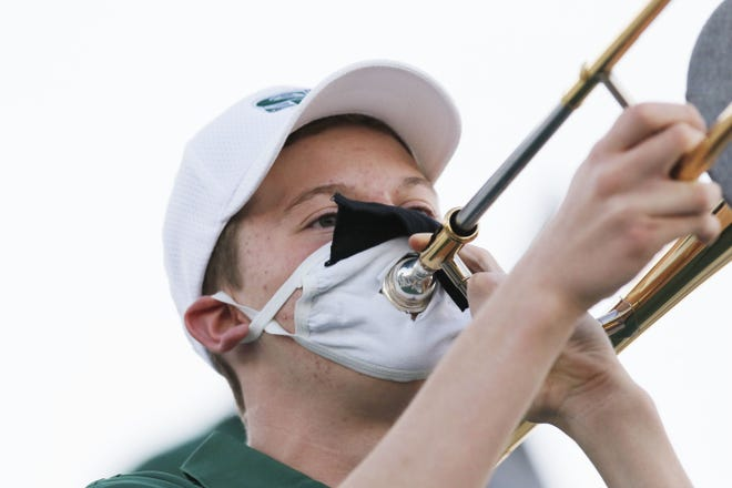 An Edmond Santa Fe band member uses a modified face mask Monday to play his trombone during the Edlam high school football game between Edmond Memorial and Edmond Santa Fe. [Doug Hoke/The Oklahoman]