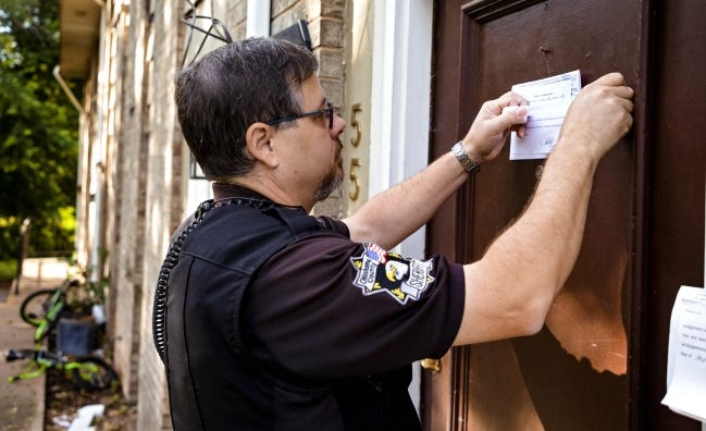 Oklahoma County sheriff's deputy Brett Price serves an eviction notice and lockout at an apartment complex in Oklahoma City prior to the COVID-19 pandemic. The CDC put a national eviction moratorium in place that is set to expire June 30.