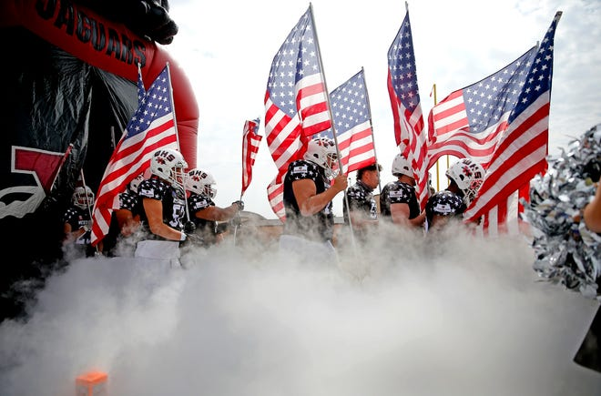 Westmoore enters the field carrying flags for a military appreciation game before the high school football game between Westmoore and Edmond Santa Fe at Moore High School in Moore, Okla., Saturday, Oct. 3, 2020. Photo by Sarah Phipps, The Oklahoman