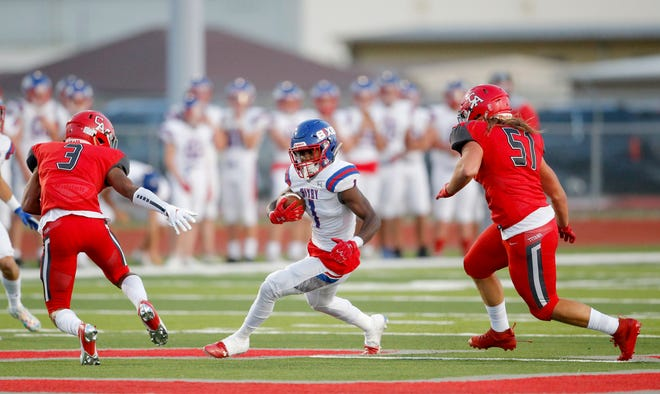Bixby's Braylin Presley rushes in between Carl Albert defenders Cobe Crews (3) and Nathan Mooney (51) during the high school football game between Bixby and Carl Albert at Carl Albert High School in Midwest City, Okla., Friday, Oct. 2, 2020. Photo by Sarah Phipps, The Oklahoman