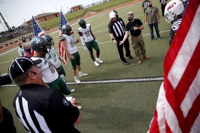 Oklahoma National Guard Sgt. Zach D'Amico tosses the coin during military appreciation ceremony before Saturday's game between Edmond Santa Fe and Westmoore. [Sarah Phipps/The Oklahoman]