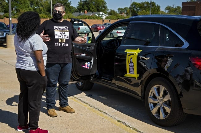 Bradley Havenar talks to Sache Primeaux-Shaw before the start of the Oklahoma Poor People's Campaign caravan protest on Monday in Oklahoma City. [Chris Landsberger/The Oklahoman]