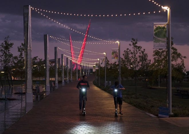 Two people ride scooters Saturday evening along the east side of Scissortail Park on the promenade connecting the park with the Skydance Pedestrian Bridge. [Doug Hoke/The Oklahoman]