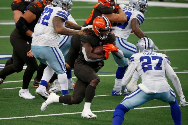 Cleveland Browns running back Kareem Hunt, center, runs the ball as Dallas Cowboys cornerback Trevon Diggs (27) defends in the second half of an NFL football game in Arlington, Texas, Sunday, Oct. 4, 2020. (AP Photo/Michael Ainsworth)