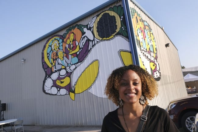 Ebony Iman Dallas stands in front of the mural she painted on the Reaching Our City (R.O.C.) building at 7710 NW 10. [Doug Hoke/The Oklahoman]